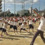 映画『みんなの学校』画像。校庭で木村先生と皆が運動する様子。