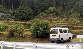 色川地区の風景。段々畑のある山都里に1台の車が停車している。