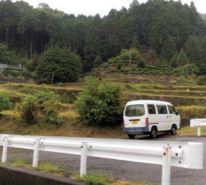 色川地区の山里。段々畑の手前に1台の車が停車している