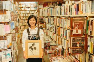飯田蝶子直筆の色紙をもった笑顔の女性。書店内で。