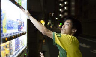 自動販売機で飲み物を買うげんちゃんの横顔