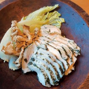 鶏肉をクロモジで香りづけした一品。木の皿に盛られて。