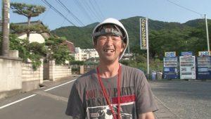 ひいくんの笑顔。ヘルメットをかぶっている。後ろには山がみえる。