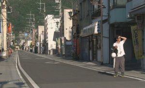映画『ひいくんのあるく町』より。まちの商店街の中にいるひいくん。白いyツを着て、片手には飲料の容器。