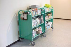 明るい緑色の3段のワゴンに積んだ本。図書室に来られない人のための移動図書。