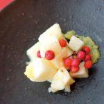 黒い皿に盛られた紅白の色合いが美しい料理。万両の赤がきわだつ。