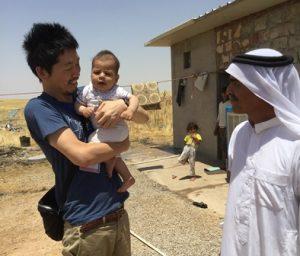 赤ちゃんを抱っこする男性。横には白い民族衣装の男性。