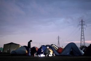 夕暮れの中に無数のテントのシルエット。明かりのまわりには人が。