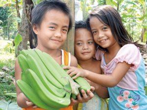 子ども3人。男の子がバナナを抱えている