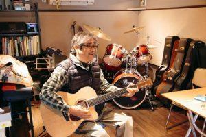 楽器がドラムに囲まれた中で男性がギターを弾いている。スタジオ。