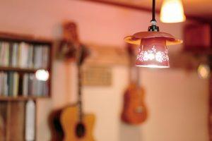 ランプに照らされたあたたかな雰囲気のカフェ店内。壁にはギターなど楽器がかかっている。