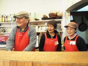 カフェのカウンターの中で笑う3人の男女。おそろいの赤いエプロンをしている
