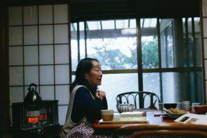 こたつにはいる女性の横顔。むこうには開けた障子。しめたガラス窓から緑がみえている。