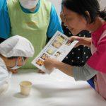 調理台を囲み、資料をみる人たち。エプロンや三角巾、マスクをしている。