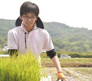 田んぼの田植えをする若い男性。メガネをかかけ、白いシャツをきている