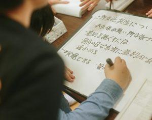 教室内、集まった子どもたちが紙に書き込んでいる様子