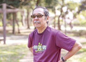 公園の中。伴走者とい書かれた紫色のシャツをきたひげの男性