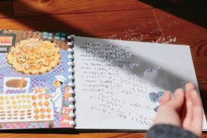 開かれた絵本。左に絵、右側に文字。文字の上に点字が打たれている透明なシート。