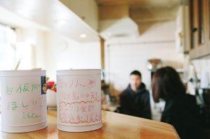 カウンターの上の缶2つ。募金のよびかけが手書きでかかれている