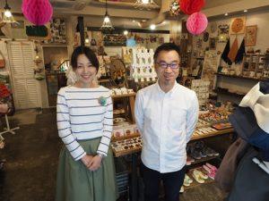 雑貨が並ぶ店内でこちらをみて立っている男女2人。