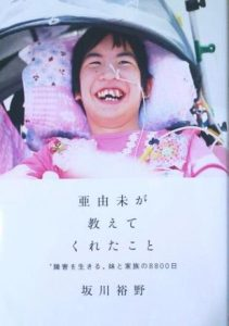 本『亜由未が教えてくれたこと』の表紙。笑顔の女性が表紙