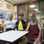 白いテーブルの向こうに並んで座る笑顔の男性3人