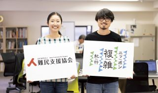 オフィスでこちらをむいて立つ男女2人。手には『難民支援協会』と『ニッポン複雑紀行』のパネルをもっている