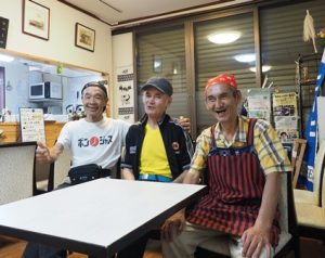 白いテーブルの向こうに並んで座る3人の男性。笑っている。