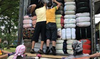トラックの荷台にびっしり積み込まれる古着。