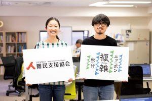 こちらをみて立っている笑顔の男女2人。手には『難民支援協会』と『ニッポン複雑紀行』のパネルをもっている