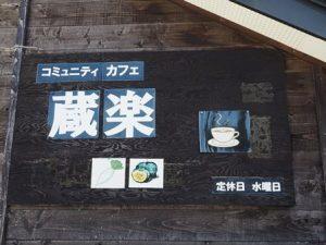 建物の壁面にあるコミュニティカフェ蔵楽の看板。カップと野菜のイラストも。