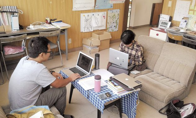 机をはさんで向き合う男女。互いにパソコンをひらいている。