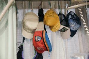 窓際にたくさんかかった帽子の間に1つウエストバッグ