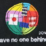 ミシンで刺繍された地球。日本のほかさまざまな国旗、色が組み合わさっている。
