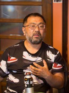 中村さんの顔。Tシャツをきて、メガネをかけている