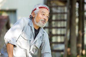 信州共働学舎代表の宮嶋さん。作業着をきて、白髪に赤いバンダナをまいている。