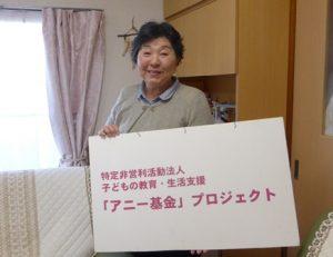 アニー基金プロジェクトの看板をもつ代表の日高さん。