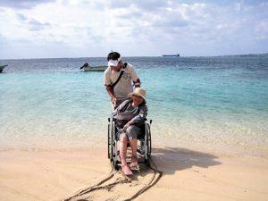 車いすに乗って、トラベルヘルパーとの旅。砂浜に車いすの跡。バックには美しい海が。