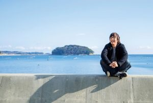 海の堤防に座るメガネをかけた若い男性、浅野さん