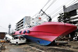 陸に乗り上げた船。周りでは電柱や建物が倒れている。