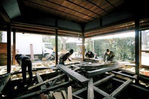 古い家屋の解体中。4人が木材の運びだしをしている