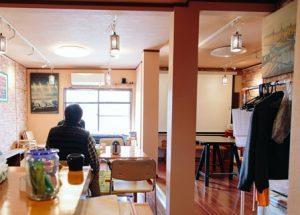 窓からひかりが差し込むカフェ店内。こちらに背をみけた男性がいる