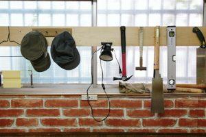 窓際にかけられた作業帽子やノコギリ、トンカチなど。