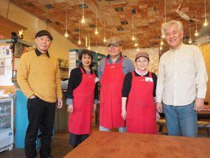 カフェのテーブルを前にして並ぶ5人の男女。真ん中の3人はおそろいの赤いエプロンをかけている