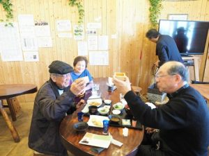 店内の様子。テーブルで楽しく飲食する男性2人。