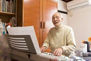 白髪の男性。イヤホンをしてキーボードをひきながら歌っている。
