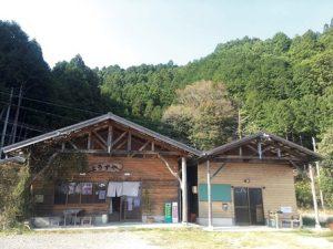 2棟並んだの木造の建物。すぐ後ろには山が迫っている