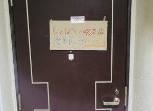 扉にはられたお店の看板。ダンボールに手書き。「しょぼい喫茶店営業中~」