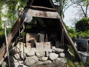 木と石でできた三角屋根のピザ窯