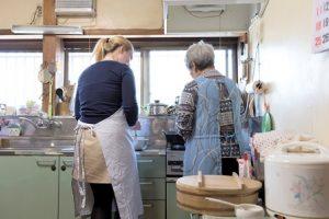 台所で調理する女性2人の後ろ姿。一人は白髪、一人は金髪。